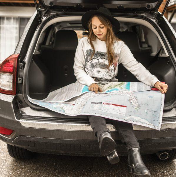 足をぶらつかせながら世界地図を広げている女性の画像