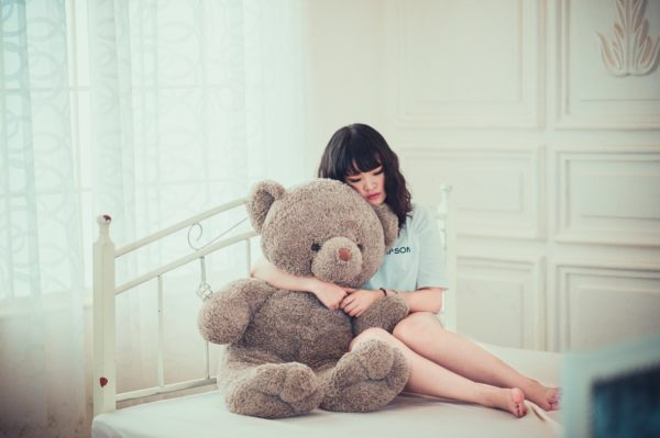 就活ブルーで落ち込んでいる女子の画像。ぬいぐるみの熊に癒やされてる画像。