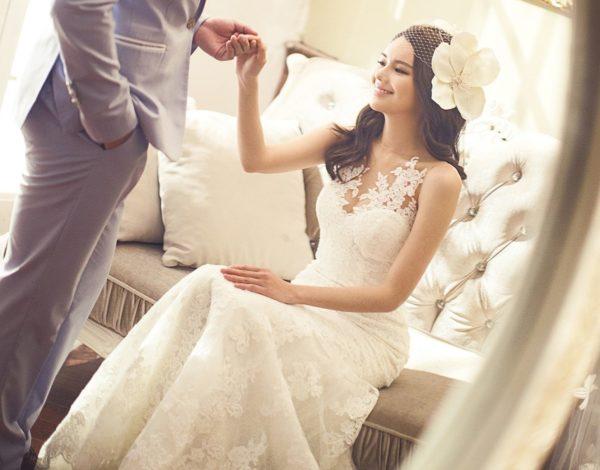 花嫁がソファから立ち上がるのを支える花婿、結婚式の直前の画像