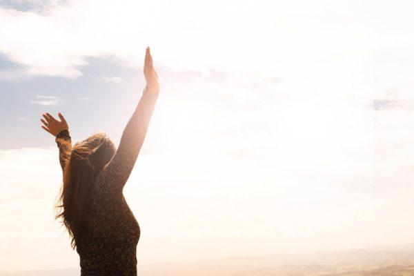 アロマオイルマッサージの効果を象徴する、明るい青空に向かって立つ女性の画像です