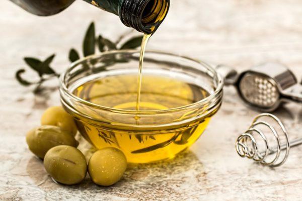 マッサージオイルとして用いる植物油(キャリアオイル)を硝子容器に移している画像です。
