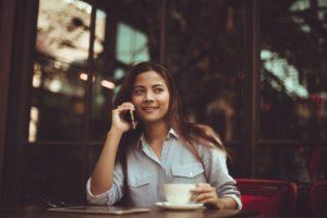 カフェでスマホから無料体験エステの予約をしている女性の画像です。ホで