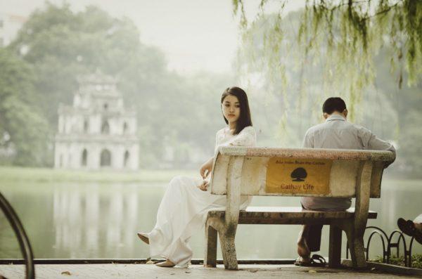 セックスレスのカップルは多く、女性が悩みを抱え込みがちです。画像は公園のベンチに座るカップル。二人の間の心の距離を感じさせます。