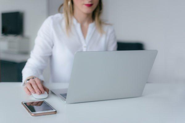 パソコンに向かってデスクで作業する女性の画像